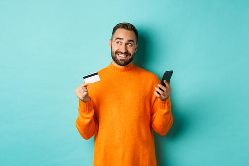 online-shopping-handsome-man-thinking-holding-smartphone-with-credit-card-paying-in-internet-store-standing-over-light-turquoise-wall